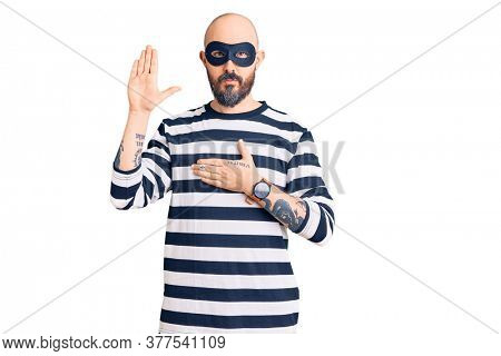 Young handsome man wearing burglar mask swearing with hand on chest and open palm, making a loyalty promise oath