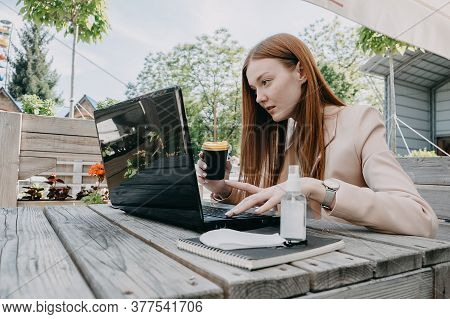 Digital Nomad, Freelancer, New Normal Work Process. Young Redhead Woman Working On Laptop In Street