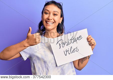 Young woman holding positive vibes banner smiling happy and positive, thumb up doing excellent and approval sign