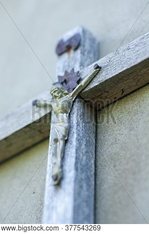 Wooden Crucifix On The Wall Closeup. Image Of Jesus. Unfocused Distant Plan.