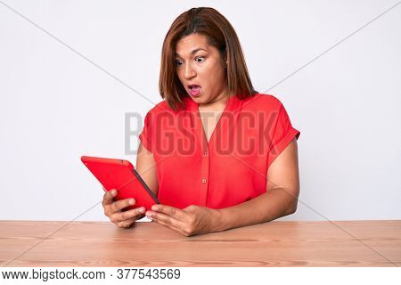 Middle age brunette hispanic woman using touchpad sitting on the table scared and amazed with open mouth for surprise, disbelief face
