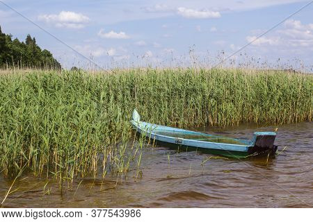 A Wooden Boat Of Emerald Color Sunken After Rain In Water