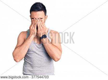 Young handsome man wearing swimwear and sleeveless t-shirt rubbing eyes for fatigue and headache, sleepy and tired expression. vision problem
