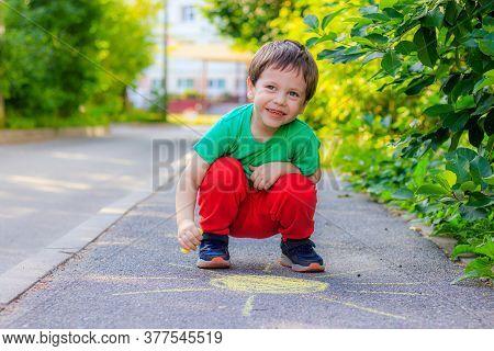 A Boy Draws The Sun On The Asphalt With Crayons . A Child Draws On The Asphalt . Childrens Drawing.