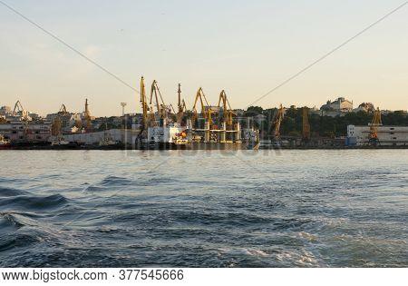 Portal Cranes In The Evening Port In Odessa, Black Sea. Waves At Sea