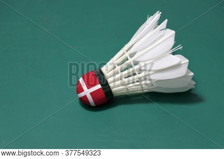 Used Shuttlecock And On Head Painted With Denmark Flag Put Horizontal On Green Floor Of Badminton Co