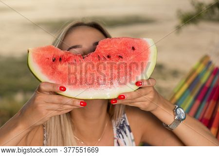 Young Girl, Raising Her Hands With A Slice Of Watermelon, Covered Their Face, A Picnic In Nature