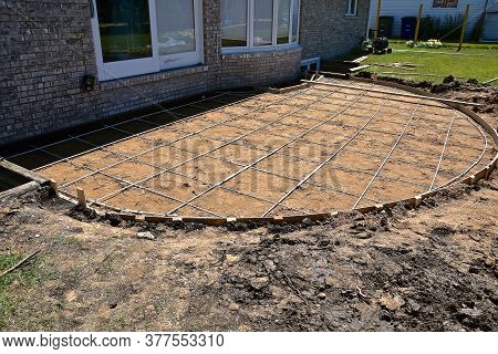 A Backyard Concrete Patio Is Being Created In The Shape Of A Semi-circle.
