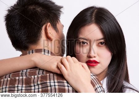 Portrait of young woman with red lips embracing man over white background