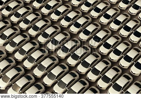 3d Rendering Of A Lot Of White Generic Sedan Cars Parked In A Dealership.