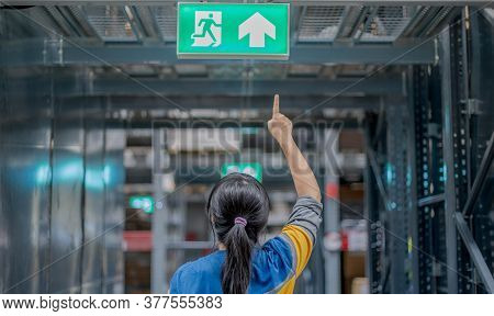The Back View Woman Pointing At The Emergency Fire Exit Sign Show The Way To Escape At The Public Ar
