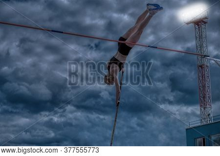 Woman Athlete Pole Vault In Background Evening Dramatic Sky And Lighting Tower