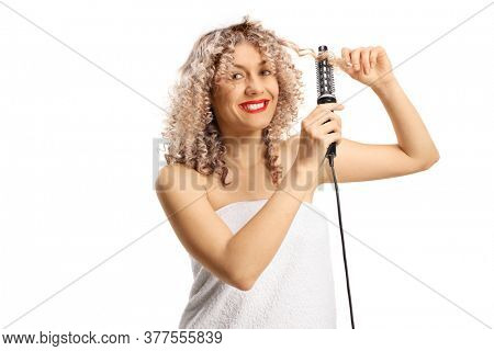 Young woman in a white towel using a curler brush isolated on white background