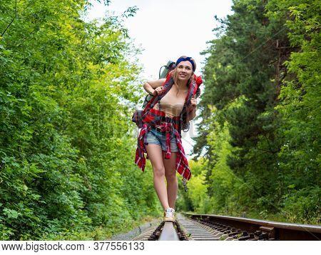 Smiley Hiker Woman Goes By Rail Through The Forest. Lifestyle Travel Portrait.