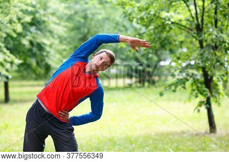 Close Up Photo Of A Man Stretcing Muscles Outdoor - Sport And Healthy Lifestyle Concept.