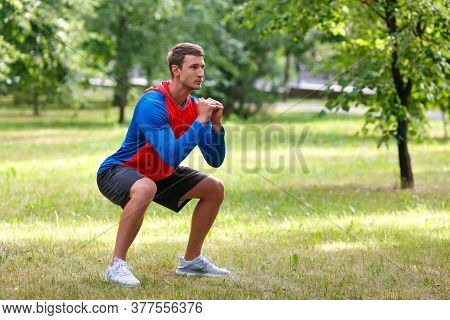 Young Attractive Man Squatting Outdoor In The Park. Concept Of An Active Lifestyle And Healthy Lifes