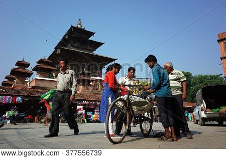 Kathmandu, Nepal - June 19, 2019: Fruit seller on bicycle sells mango to local people on Kathmandu street near Durbar square