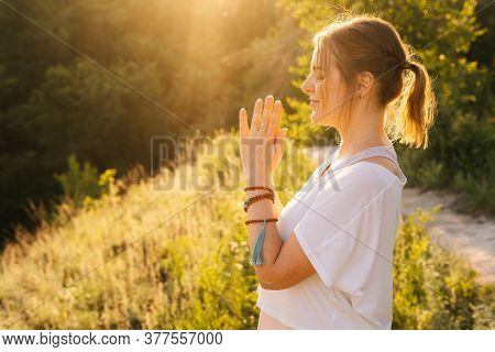Middle Shot Portrait Of Hands And Faces Of Meditating Woman Doing Namaste Yoga Pose Background Of Br