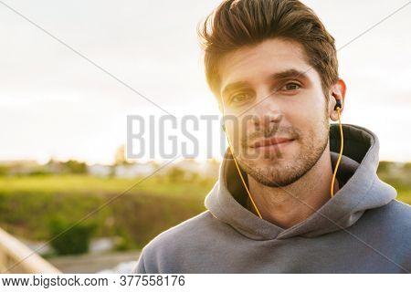 Image of athletic bristle sportsman using earphones and looking at camera on city bridge