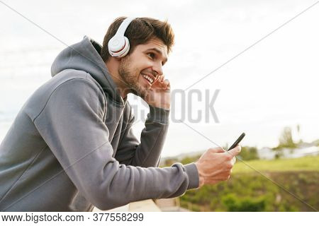Image of joyful sportsman using headphones and cellphone while leaning on railing outdoors