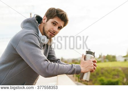 Image of athletic sportsman with headphones holding water bottle while leaning on railing outdoors