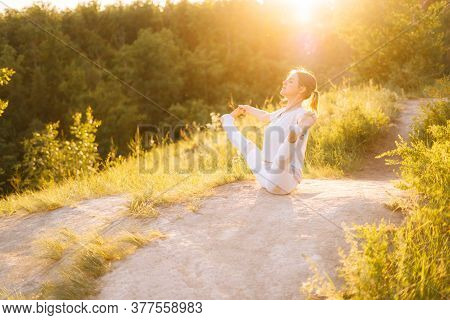 Young Fit Woman Performing Yoga Posture Boat With Toe Hold, Outside Evening On Background Of Bright