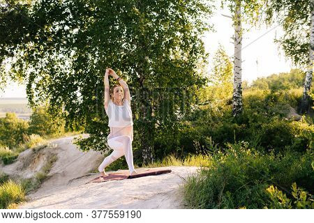 Attractive Young Woman Doing Warrior Yoga Asana Pose On Top Of Rock Background Of Beautiful Landscap