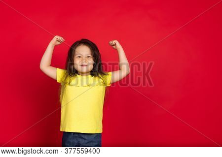 Strong, Winner. Beautiful Little Girl Isolated On Red Background. Half-lenght Portrait Of Happy Chil