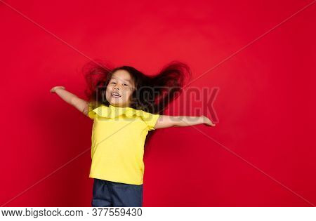Happy, Hair Blowing. Beautiful Little Girl Isolated On Red Background. Half-lenght Portrait Of Happy