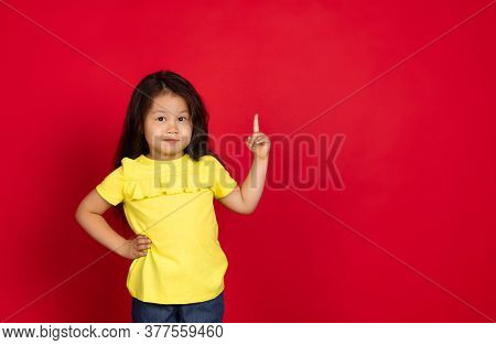 Pointing. Beautiful Little Girl Isolated On Red Background. Half-lenght Portrait Of Happy Child Gest