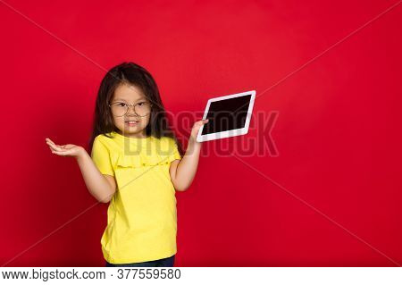 Showing Blank Tablets Screen. Beautiful Little Girl On Red Background. Half-lenght Portrait Of Happy