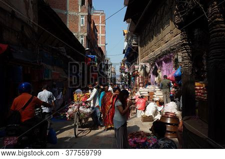 Kathmandu, Nepal - June 17, 2019: Local daily life on street, Fruit seller walking with mango on bicycle on crowded narrow street in old town