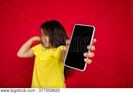 Showing Blank Phones Screen. Beautiful Little Girl On Red Background. Half-lenght Portrait Of Happy
