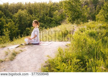 Happy Woman Meditating Sitting On Yoga Mat In Lotus Pose With Closed Eyes, Holding Her Hand In Om Po