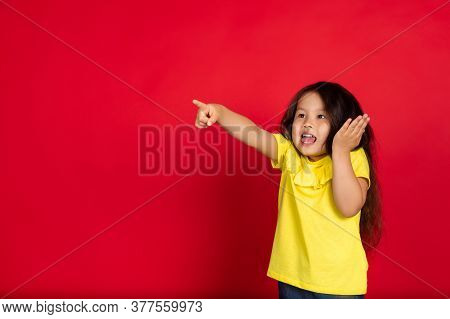 Shocked Pointing. Beautiful Little Girl Isolated On Red Background. Half-lenght Portrait Of Happy Ch