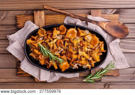 Fried Chanterelle Mushrooms With Onions And Rosemary On A Dark Wooden Background. Selective Focus.