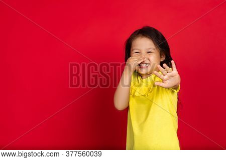 Disguasted, Rejecting. Beautiful Little Girl On Red Background. Half-lenght Portrait Of Happy Child