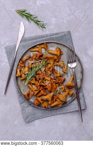 Fried Chanterelle Mushrooms With Onions And Rosemary On A Grey Slate Background. Selective Focus.