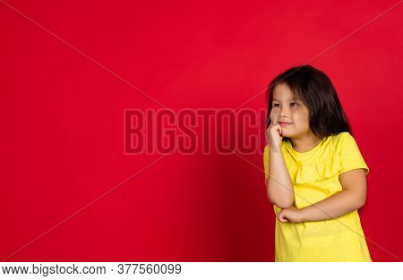 Dreamful, Thoughtful. Beautiful Little Girl Isolated On Red Background. Half-lenght Portrait Of Happ