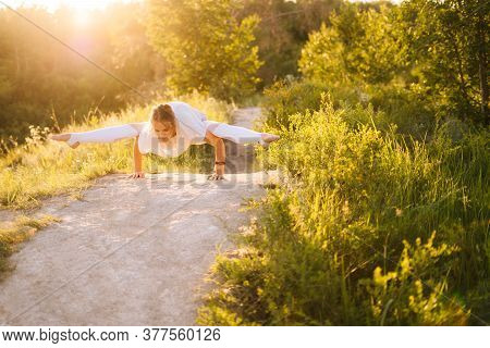 Concentrated Sporty Woman Performing Firefly Pose. Girl Doing Advanced Yoga Exercises, Leaning On Ha