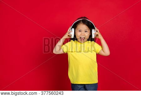 Listening To Music, Dancing. Beautiful Little Girl On Red Background. Half-lenght Portrait Of Happy