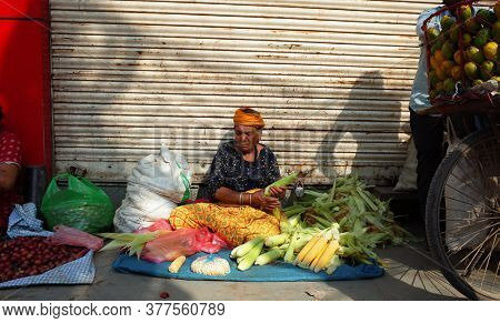 Kathmandu, Nepal - June 19, 2019: Local daily life on street, Old nepali woman selling corn cobs sitting on ground in traditional clothes, Street market