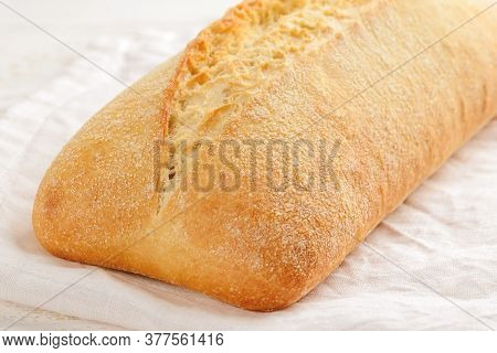 Close-up Of Whole Fresh Tasty Ciabatta Bread On A White Linen Napkin Over A Wooden Table. Traditiona