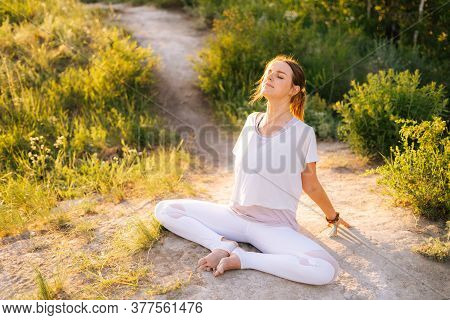 Happy Woman Sitting In Lotus Pose And Doing Bend In Back Outside In Park Evening On Background Of Su