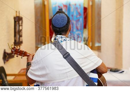 Rabbi Of The Jewish Reform Movement Is Wrapped In A Tallit, Prays, And Plays The Guitar In Front Of