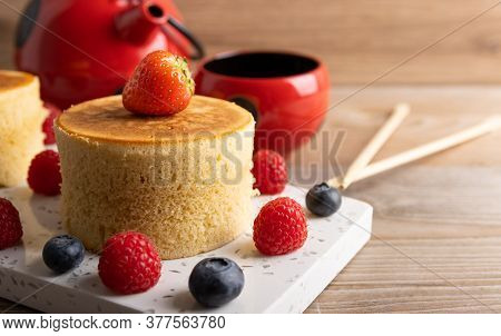 Homemade Japanese Hotcakes On A Wooden Background With Raspberries, Blackberries And Strawberries An