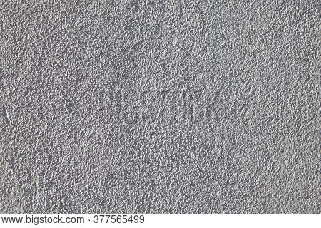 Light Gray Texture Of Granular Painted Plaster. The Surface Of A Rough Plastered Wall Is Off-white,
