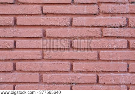 Red-brown Brick Texture Of The Painted Wall. Low Contrast Pink Background.