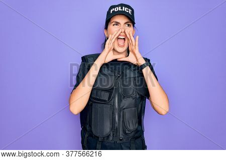 Young police woman wearing security bulletproof vest uniform over purple background Shouting angry out loud with hands over mouth