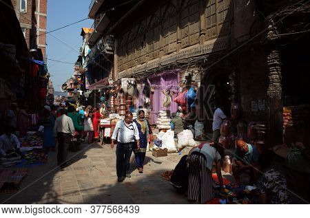 Kathmandu, Nepal - June 17, 2019: Local daily life on street, Sun shining on nepali man and woman walking on narrow shopping street in old town
